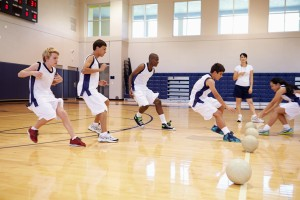 Students run on a basketball court in PE class