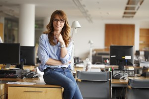 School secretary wears glasses and sits at a desk