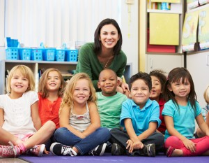 Preschool teacher sits with seven small children.